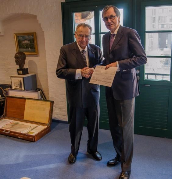 Dr. Ottmar Gast, Sprecher der Geschäftsführung der Hamburg Süd, überreicht Prof. Peter Tamm eine Spende.