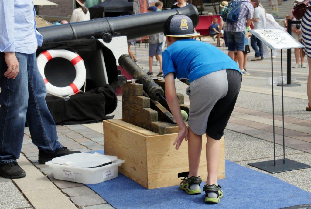 Junge übt das Kanonenschießen im Piraten Parkour am Vorplatz des Internationalen Maritimen Museum Hamburg. Der Familiensonntag ist Teil der Veranstaltungsreihe Sommer in der HafenCity.