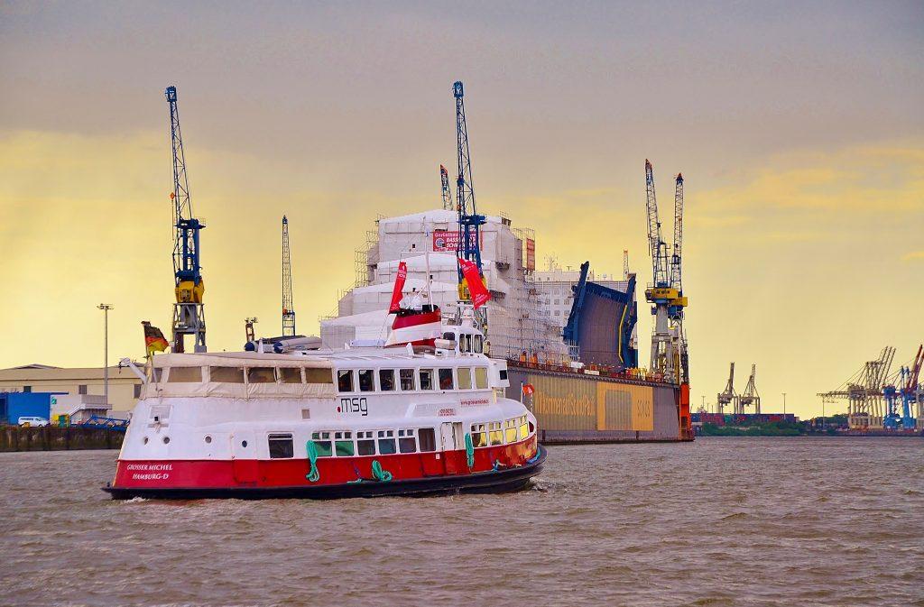 Die Hafenfähre Grosse Michel fährt gegen Sonnenuntergang im Hamburger Hafen am Werft von Blohm und Voss vorbei.