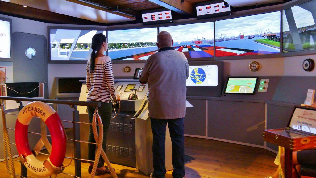 Eine Besucherin des Internationalen Maritimen Museum Hamburg manövriert ein riesen Containerschiff am Schiffsführungssimulator.